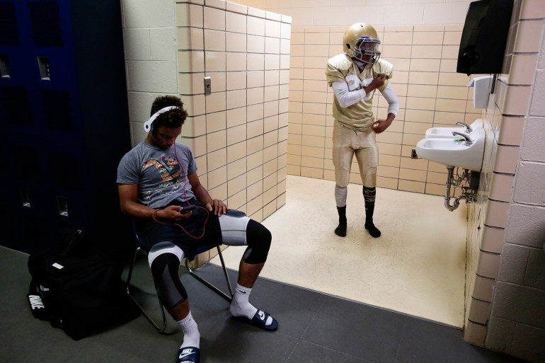 Rob Anderson, right, checks out his new uniform in the locker room mirror as teammate Tavarus Parker, left, listens to music before the Reigning Sports Academy Thunder's first varsity high school football game against Bishop Hartley on Friday, Aug. 28, 2015 at Bishop Hartley High School in Columbus, Ohio. The Thunder are composed of players throughout Columbus who don't play for their high school football team for a variety of reasons, including grades, behavior, or issues with other players or coaches. For many of the players, the structured team environment keeps them out of trouble.