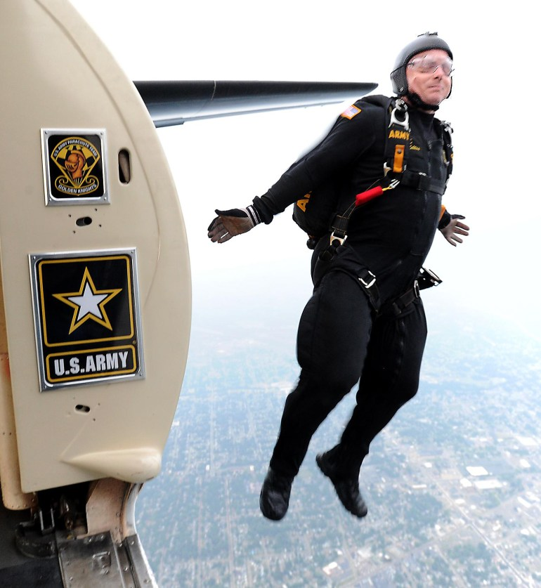 United States Army Parachute Team Golden Knights team leader SFC Thomas Melton exits the plane as his team heads to Tom Benson Hall of Fame Stadium to deliver the game ball.