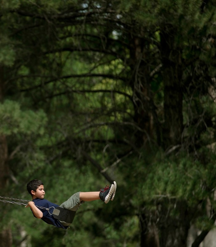 Dashawn Portillos, 8, bites his lip as he swings high into the air at City Park Wednesday afternoon August 20, 2014 in Pueblo, Colo. The youngster was at the park with family enjoying time at the park prior to the beginning of school. (Bryan Kelsen, The Pueblo Chieftain)