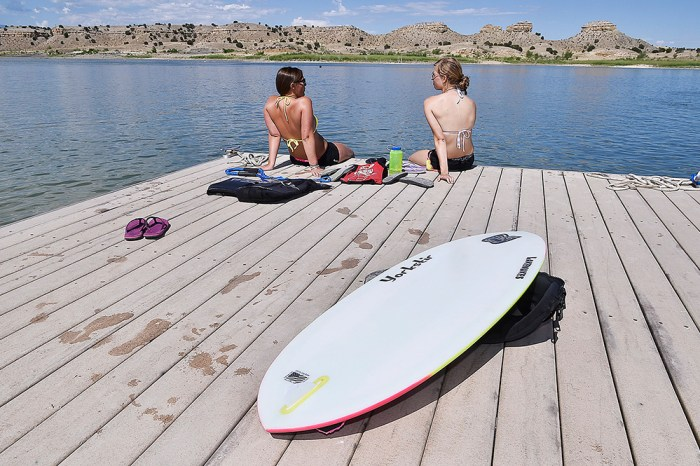 Hannah York, 28 (left) and Katelyn Lynch, 20, sit on a dock as there turn to wakesurf at the Colorado Wakesurfing Open held at Lake Pueblo on July 12, 2014. (John Jaques,The Pueblo Chieftain)