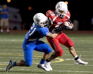 Centennnial's Caleb Miranda, right, gains yardage before begin tackled by Central's Nikko Valdez during the first half of the Bell Game at Dutch Clark Stadium on Sept. 26, 2014 in Pueblo, Colo. (Chris McLean, The Pueblo Chieftain)