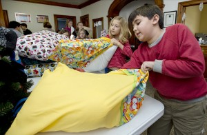 McClelland School, fourth grade student council members Noah Nizami, 9, right and Julia Paulman, 9, along with other student council members stuff pillows into pillow cases in the school's lobby Wednesday December 10, 2014 in Pueblo, Colo., as part of a school-wide pillow drive. The pillows were donated to the Pueblo CASA (Court Appointed Special Advocates) for children. (Bryan Kelsen, The Pueblo Chieftain)