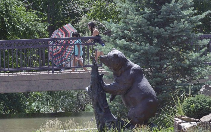 Julie Riley ,12, (right) pushes her niece Lizzy Zamora-Riley, 9, and nephew Dominic Lucero ,11, months-old over a footbridge on the HARP Riverwalk as a statue of a bear looms in the foreground. (John Jaques,The Pueblo Chieftain)
