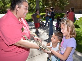 Christy Fidura (left) a Pueblo Colo. zoo volunteer holds 'Marvin' the bull snake as Richard Fransua Jr.,3, (middle) and his sister Angelisia Fransua ,8, pet the snake at the Red Pande Day activities on Sept. 19, 2015.(John Jaques,The Pueblo Chieftain)