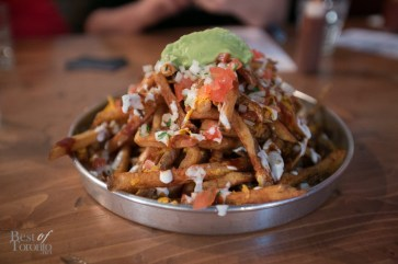 Baja fries made with russett potatoes, cheddar cheese, adobo chipotle sauce, lime crema, onion, cilantro and house made guac