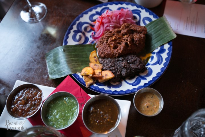 """Cochinita Pibil"" with Southern style pork butt in ahciote and orange juice marinade, roasted in banana leaves, pulled and served with fried plantains, pickled red onions and salsa Pancho (habaneros, tomatillo, serrano salsa)"