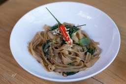 "For a vegan dish, we have ""Pad See Ew"" with traditional broad rice Thai noodles, wilted mustard greens, savoy cabbage, peanut-candied bird chili garnish. The candied chili is interesting but watch out because it is potent."