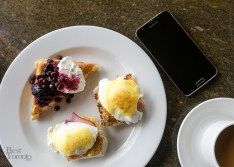 Eggs benedict, waffle with toppings, coffee and a Samsung Galaxy S5