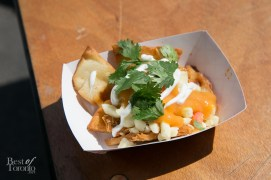 Nachos with delicious crispy naan bread topped with butter chicken, cheese, mango lime sauce, crema and garnished with cilantro by Curbalicious. Loved this!