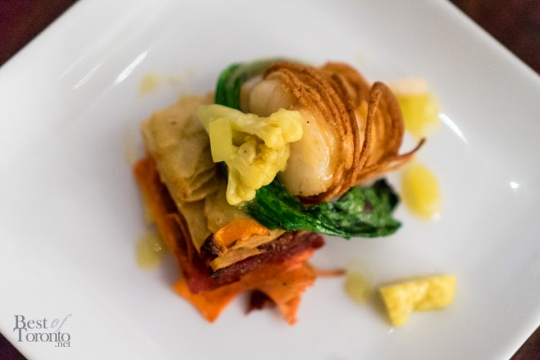 Potato wrapped cod, root vegetable and salt meat pave, mustard pickle vinaigrette