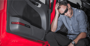 Tired truck driver with head in his hands