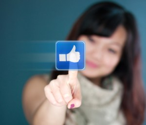 woman clicking Facebook like button