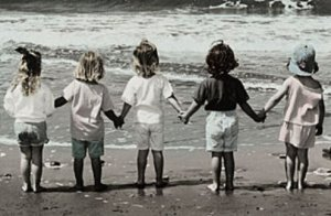 girls holding hands at beach