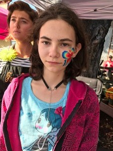 Annabelle with her butterfly face painting and the artist by her
