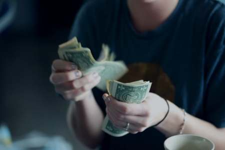 Woman counting dollars. Image source: Unsplash