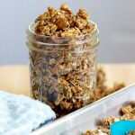 A mason jar overflowing with nutty coconut granola clusters