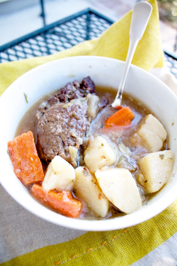 a bowl of pot roast with tender meat, potatoes, and carrots