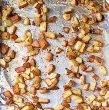 a foil-lined sheet pan with life-changing super crispy roasted potatoes scattered on it
