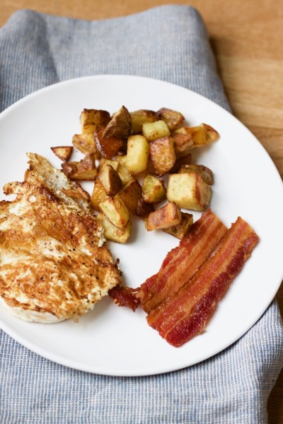 a plate with life-changing super crispy roasted potatoes, a fried egg, and bacon