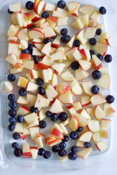 a glass pan of cut up apples and blueberries