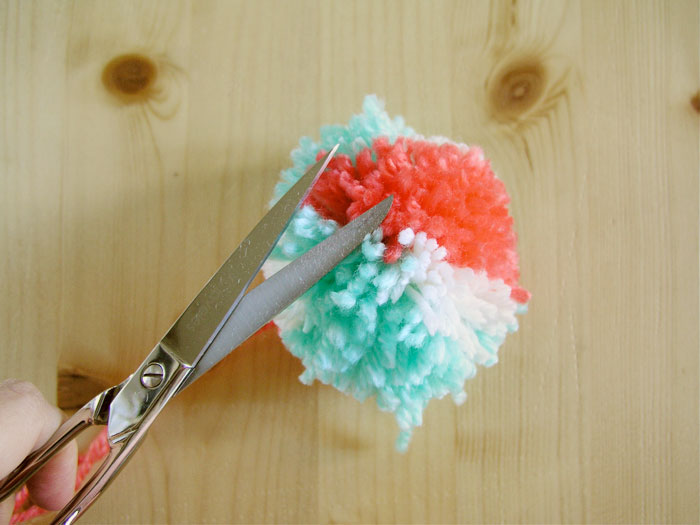 Shape the pom pom round with the scissors
