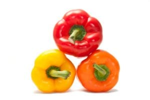 Three colored peppers stacked in a triangle, isolated on white.