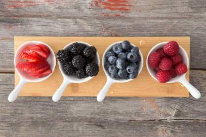 Taster dishes of assorted autumn berries viewed from above arranged on a wooden board on a rustic, kitchen table including whole fresh blueberries, blackberries, raspberries and sliced strawberries