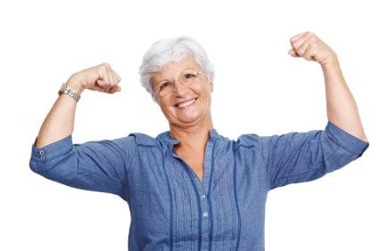 Portrait of a fit old woman flexing her arms and showing her muscles against white background