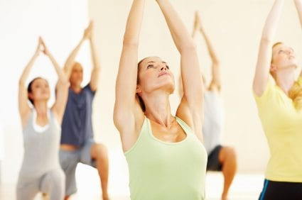 Portrait of relaxed woman stretching with other people at class