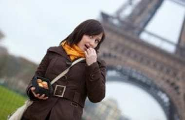 Happy young woman eating macaroons near the Eiffel Tower