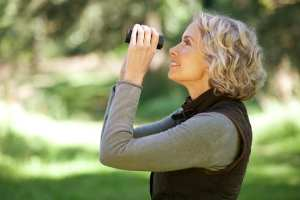 Mature woman outdoors, looking through a pair of binoculars