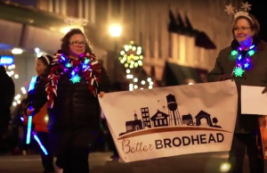 Jen Wichita holds a Better Brodhead banner while walking in the 2017 Brodhead Fire and Ice parade.