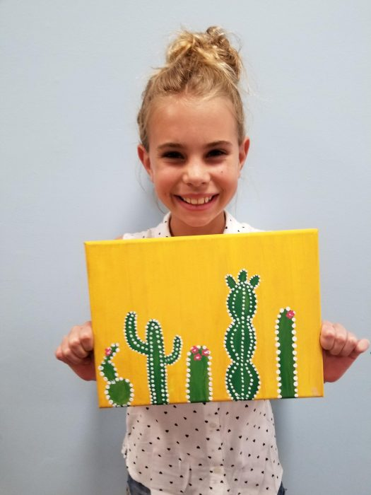 Young Girl holding a painting of cacti