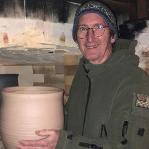 Smiling man wearing a hat, sweater, holding a pot.