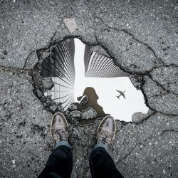 black and white reflection, with the bottom of a person's legs looking into a pothole full of water