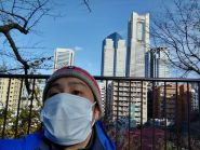 Man wearing mask and hat in front of buildings.