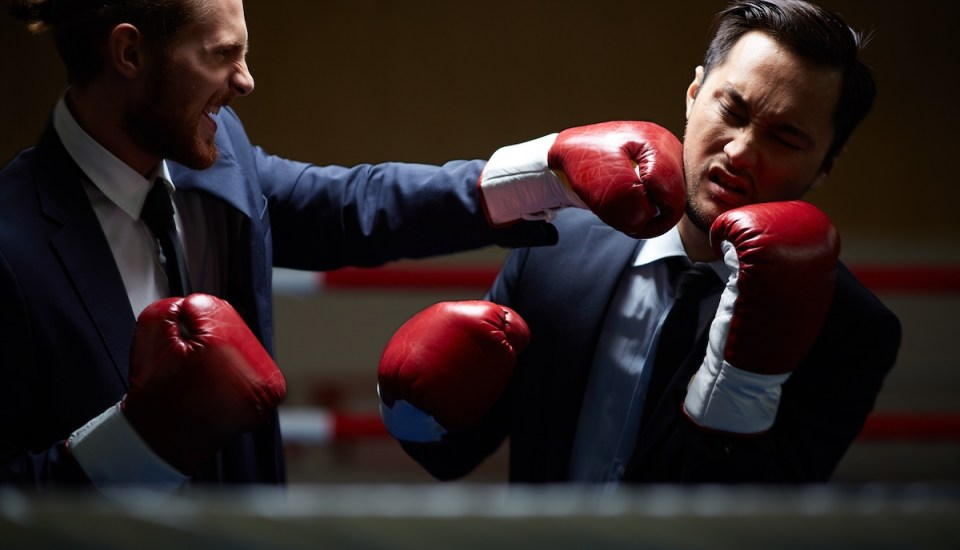 Men in business suits boxing in a ring