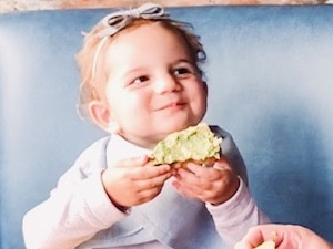 Child smiling at Bettolino Kitchen while eating avocado bread