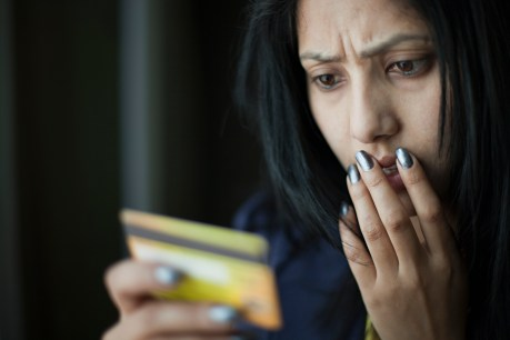 Indoor image of a shocked and worried young woman looking at credit card she is holding and putting her other hand on her face while giving frowning expression on face. One person, horizontal composition with copy space and selective focus.
