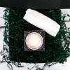 Sur un fond blanc, au centre de l'image on peut voir une boite carrée vert foncé ouverte remplie de confettis placés de façon désordonnés à l'intérieur et une partie à l'extérieur de la boite. Au centre de cette boite, au-dessus des confettis on peut voir placée à plat une boite carrée de cotons démaquillants réutilisables. Au centre de cette boite, on peut voir un cercle découpé dans la boite qui permet de voir le produit à l'intérieur de la boite. De biais, au-dessus de cette boite de cotons démaquillants on peut voir un petit sac en filet muni d'une fermeture éclair celui-ci est plié en deux sur la longueur et est placé à plat.