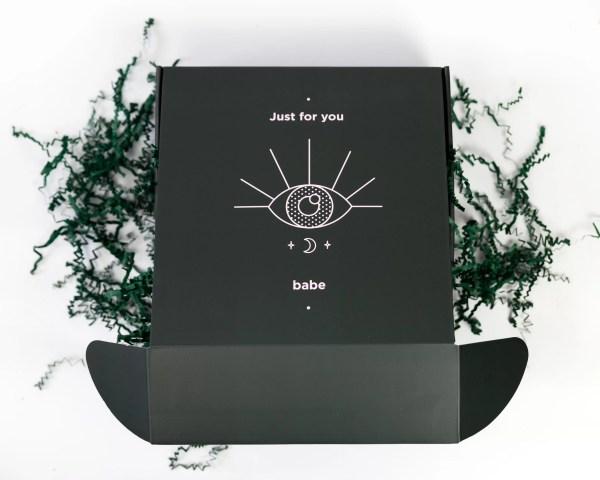 Sur un fond blanc, au centre de l'image on peut voir une boite carrée vert foncé semi-ouverte laissant déborder des confettis placés de façon désordonnés à l'extérieur de la boite. Sur le dessus de cette boite, on peut voir des symboles et des écritures en rose pâle.