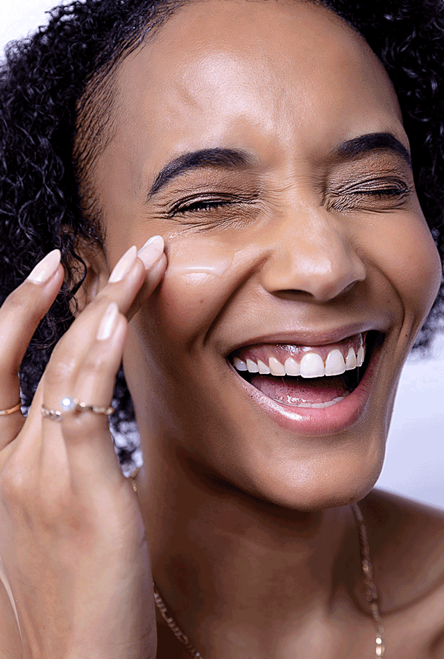A woman smiling while applying cream on her face