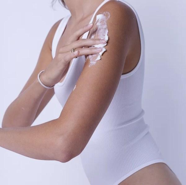 femme qui s'applique de la lotion hydratante corporelle