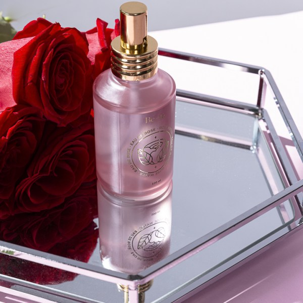 eau de rose sur plateau de miroir avec roses