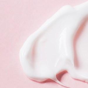 texture de la lotion hydratante corporelle sur fond rose