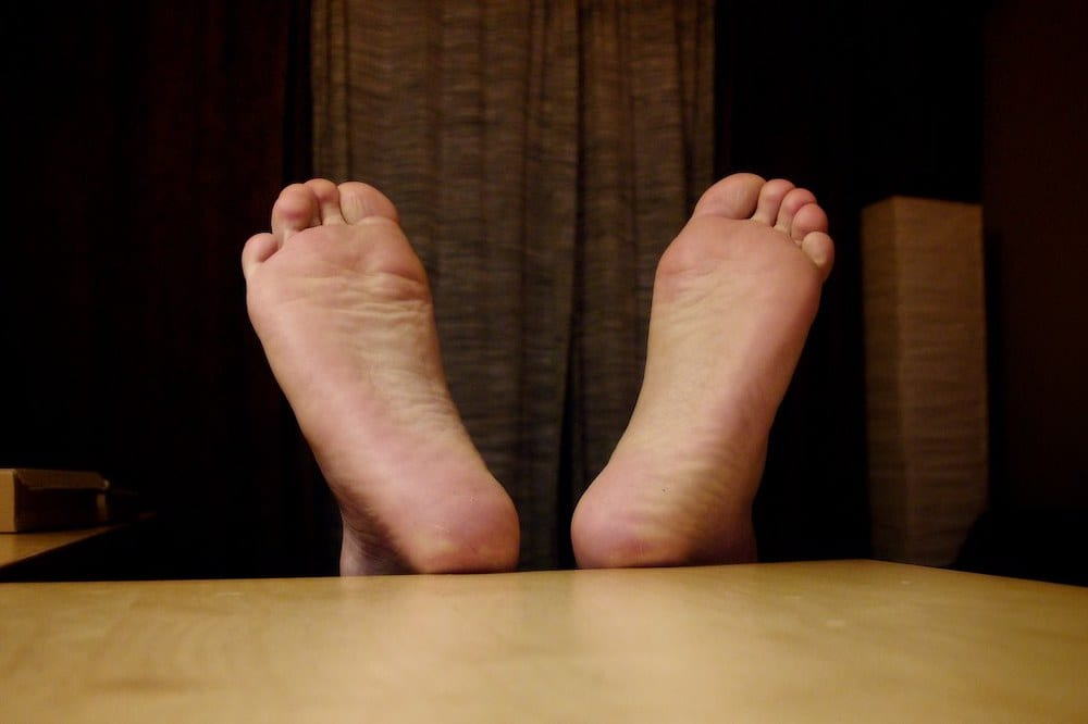 Bare feet propped up on a table