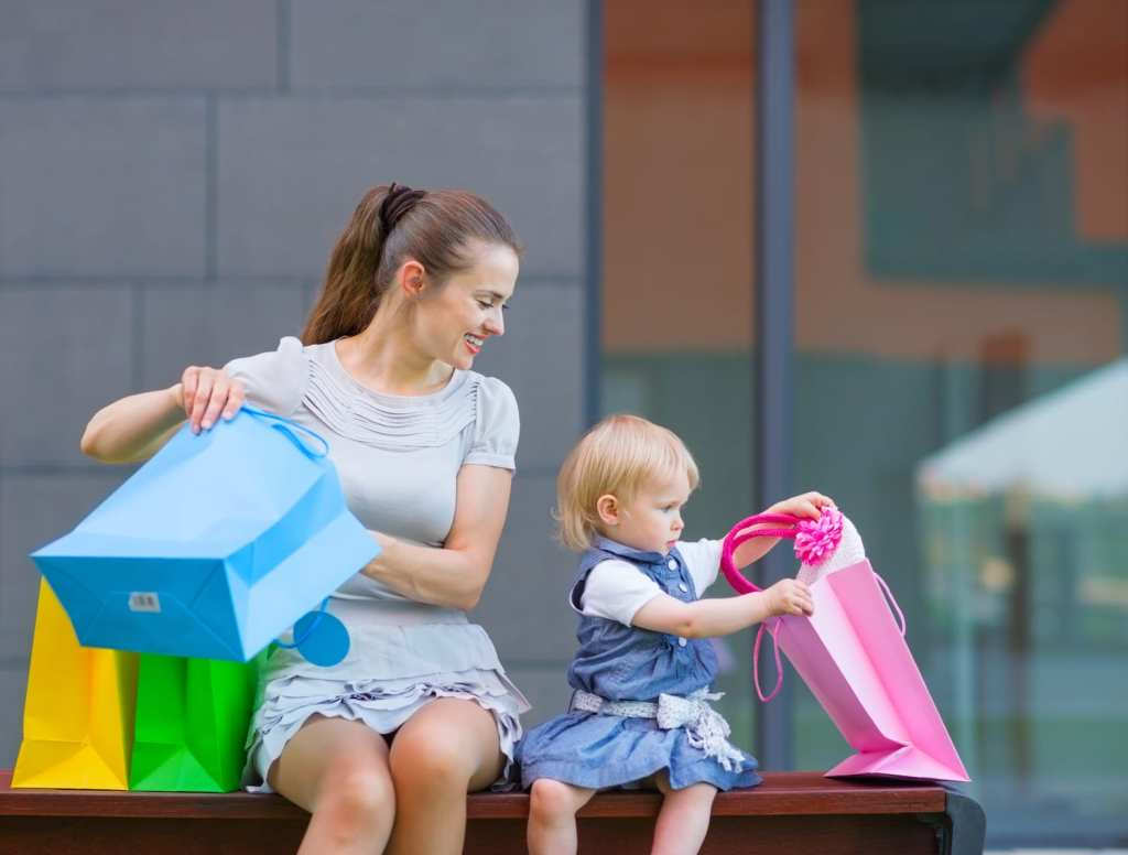 mom and toddler looking at shopping bags