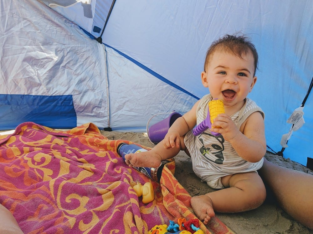 baby at the beach under a tent