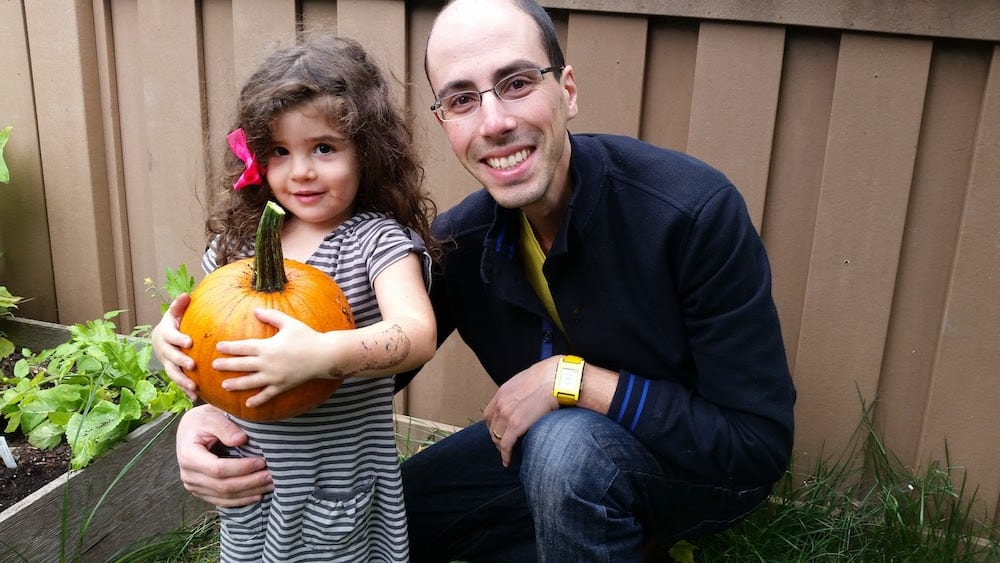 Toddler holding a pumpkin with her dad