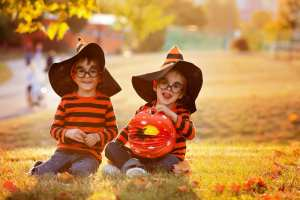 Two boys in a park dressed in Halloween costumes